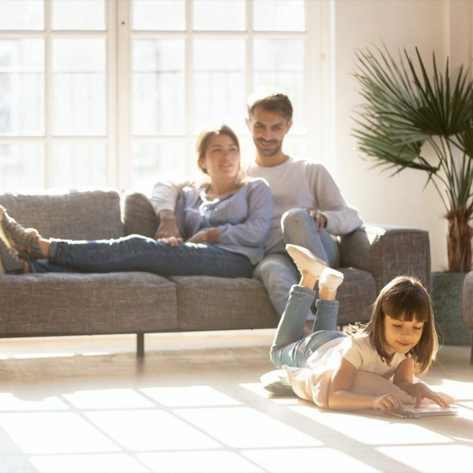 Family enjyng in living room | Broadway Carpets, Inc